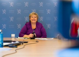Norwegian prime minister Erna Solber sits at a table.