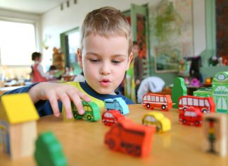 a child playing with cars at a kindergarten.