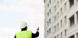 Back view portrait of unrecognizable engineer holding plans standing at construction site outdoors, copy space