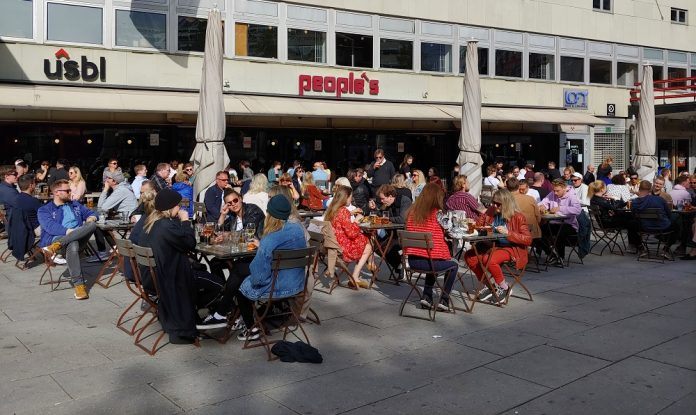 A group of people sitting at a bar outside.