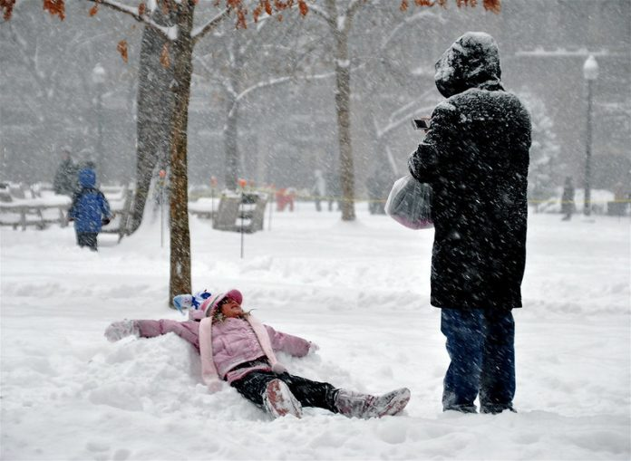 A little girl makes a snow angel